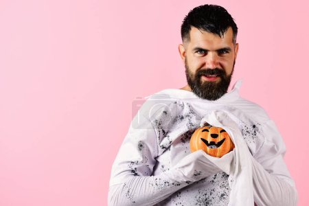 Photo for Man with smiling face isolated on pink background, copy space. Halloween and celebration concept. Halloween character in white long sleeved ghost costume. Guy with beard holds smiling orange pumpkin - Royalty Free Image