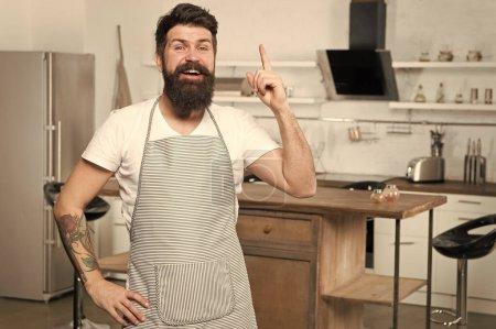 Photo pour J'ai une nouvelle idée de sa recette. Doigt heureux de garde de cuisinier soulevé dans la cuisine. Chef barbu suivant la recette pour impressionner. Dîner de cuisson avec la recette traditionnelle. Préparation du repas avec recette de cuisson. - image libre de droit