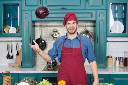 Photo pour Catch it. Handsome cook in kitchen. Chef following recipe. Cooking dinner with traditional recipe. Preparing meal. Healthy food. Professional kitchen. Traditional cuisine. Man at kitchen concept. - image libre de droit