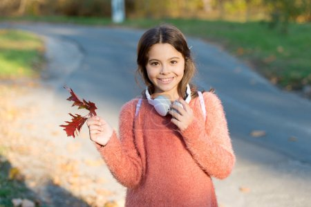 Photo for Kid girl relaxing autumn leaf with modern wireless headphones. Listening songs. Melody for good mood. Drive by song. Enjoy music outdoors fall warm day. Audio file. Music for autumn cozy mood. - Royalty Free Image