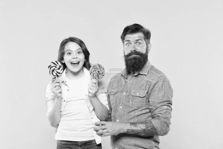 Photo for Sharing sweets with dearest people. Daughter and father eat sweet candies. Sweet childhood. Girl child and dad hold colorful lollipops. Sweet dessert. Bearded hipster good daddy for adorable daughter. - Royalty Free Image