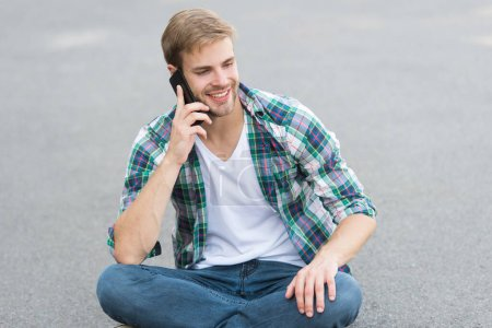 Photo for Nice talk. man sit on ground. carefree student. free time spending. summer fashion. handsome man checkered shirt. male fashion. student relax speaking on phone. guy has friend call. street style. - Royalty Free Image