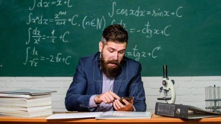 Photo pour Enseignement mobile. L'homme barbu tient le téléphone portable à la leçon. Le professeur utilise l'internet mobile. E-learning via un appareil mobile. Smartphone comme outil éducatif. Aide par téléphone portable dans l'éducation en ligne . - image libre de droit