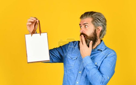 Photo for Bearded man hold paper bag. presents. delighted man shopping online. surprised hipster making purchases at electronics store. Positive man enjoying shopping. Own business. Choosing the best. - Royalty Free Image