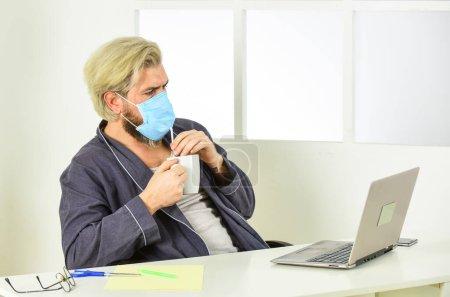 Photo pour Bureau à domicile. Travail à distance. Travailleur en masque médical. Tout ce dont vous avez besoin pour une journée productive. Totalement protégé. Le port d'un masque protège contre le coronavirus. L'homme en masque boit du café de thé avec de la paille. Hygiène grave. - image libre de droit