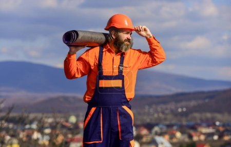 Photo for Roof installation. Man hard hat work outdoor landscape background. Building house. Apply plastic coatings membranes fiberglass or felt over sloped roofs before applying shingles. Roofer repair roof. - Royalty Free Image