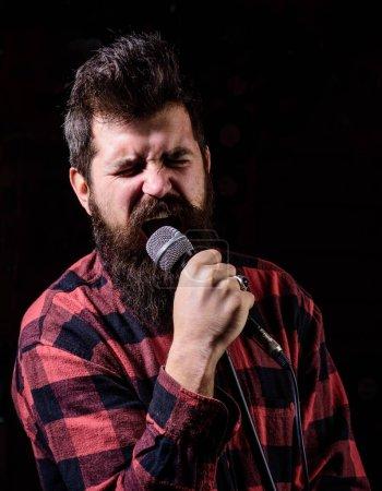 Photo pour Karaoké chante la chanson au microphone, chanteur avec barbe sur fond noir. Un homme sérieux tenant un micro dans sa main au karaoké chante une chanson . - image libre de droit