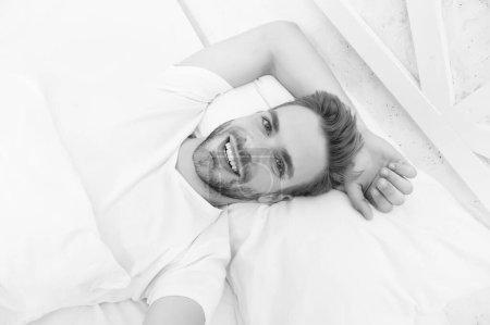 Photo pour Un bel homme se relaxant au lit. Établir des habitudes de sommeil nocturne régulières. Pratiquez des activités calmantes telles que la méditation avant d'aller au lit. Concept de sommeil sain. Conseils favorisant des habitudes de sommeil saines. - image libre de droit