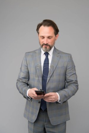 Photo for Mature businessman answer email. professional business man in formal suit. confident male use mobile phone. trying to help someone. ceo in office jacket typing sms on smartphone. - Royalty Free Image