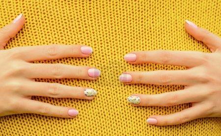 Photo pour Un concept de câlin. Belles mains touchant fond tricoté. Spa et soins des ongles. Des ongles sains. Manucure à ongles. Beauté et mode. Les ongles de marée se ferment. Fémininité et tendresse. Procédure de soins à la crème . - image libre de droit