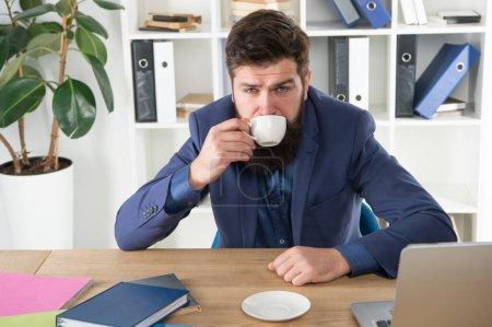 Photo pour Mon énergie. Les habitudes de vie au bureau. Respectable PDG. Premier café. Homme beau patron assis dans le bureau à boire du café. Espace de travail confortable. Bonjour. Bonjour. Costume barbu hipster formel relaxant avec café. - image libre de droit
