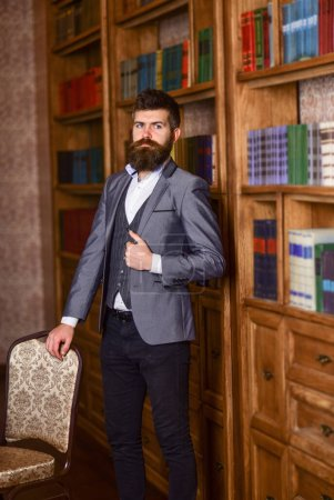 Photo for Aristocrat stands in luxury interior near empty chair. Bearded man in expensive suit in his cabinet. Nobility, luxury lifestyle, success, vintage concept. Rich man with calm face looks successful. - Royalty Free Image