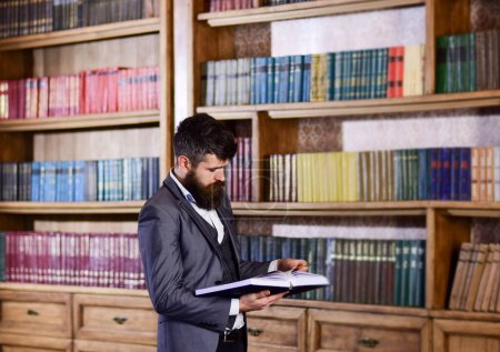Photo for Mature man with serious face reading. Professor stands in big library and holds book. Bearded man in expensive suit in his cabinet. Study, learn, read, teach, library, history, literature concept. - Royalty Free Image