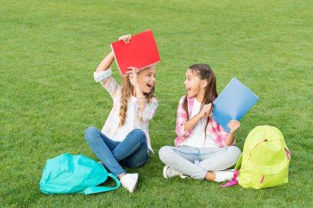 Photo pour Amuse-toi bien. petits amis enfants se détendre sur l'herbe. retour à l'école. littérature pour les filles. faire des devoirs ensemble. trouver quelque chose d'intéressant dans le livre. prendre des notes. passer du temps libre après l'école. - image libre de droit