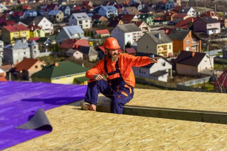 Photo for Building skills. roofer wear safety uniform inspection. Roofer working. Roofer working tool. Construction Industry and Waterproofing. roofer working on roof structure of building on construction site. - Royalty Free Image