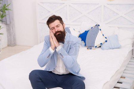 Photo pour Tout habillé et nulle part où aller. Hipster endormi assis sur le lit. Barbu avec un look somnolent dans les vêtements de formalerie. Rêve. Je me sens fatigué et endormi. Attendre le rend endormi . - image libre de droit