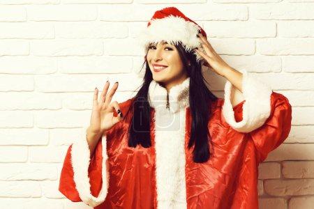 Photo pour Jolie fille santa sexy mignon ou souriante femme brune en pull rouge avec Noël ou chapeau de Noël et montrant ok sur fond de mur de brique blanche - image libre de droit