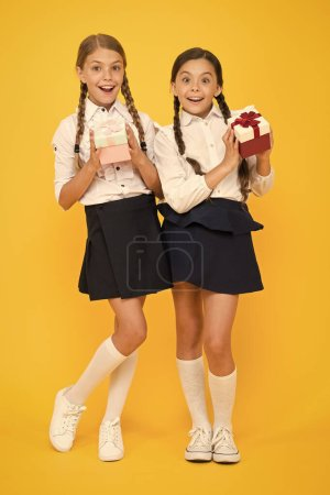 Photo for Best pupils award. Holiday celebration. Sharing gifts. Rewarding excellent pupils. Girls opening gifts yellow background. Classmates tidy pupils open gifts boxes. Educational program for gifted kids. - Royalty Free Image