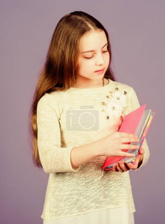 Photo for Learn more. Girl hold book violet background. Kid show book notepad. Book concept. Childhood literature. Development and education. Reading skill. Personal diary. Notepad planner. School stationery. - Royalty Free Image