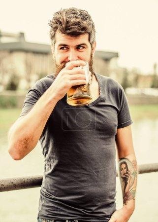 Photo pour Des bières claires ou des stouts sombres les boivent toutes. Homme avec barbe et moustache tenir verre de bière à l'extérieur. Le type se repose avec de la bière fraîche. Hipster détendue boire de la bière en plein air. Café terrasse d'été . - image libre de droit