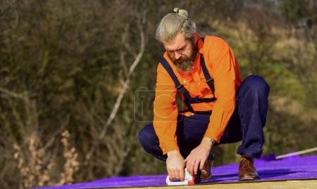 Photo for Concentration. Flat roof installation. roofing felt. Roofer worker in special protective work wear. new roof under construction building. builder use stapler. professional master repair roof. - Royalty Free Image