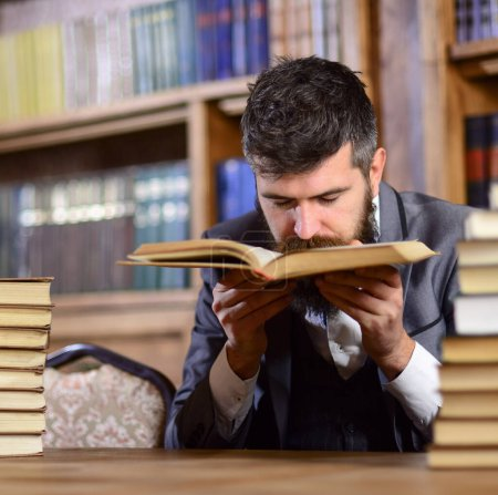 Photo for Man with beard in classic suit, scientist or professor sniffs smell of antique book in library near pile of books, bookshelves on background, defocused. Treasures of science concept. - Royalty Free Image