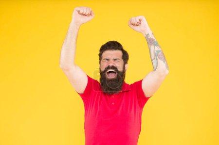 Photo pour C'est la victoire. Joyeux hipster avec les mains levées fond jaune. L'homme barbu célèbre la victoire. Le jeu et les paris. Profitant de la victoire. Victoire ou succès. Gagnant et champion. - image libre de droit