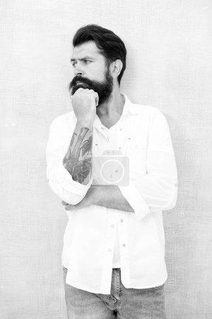 Photo pour Mannequin sexy posant. homme barbu porter une chemise blanche. mode décontractée masculine. collection d'été. modèle masculin réfléchi en chemise blanche. brutal hipster caucasien avec moustache. bel homme à la barbe. - image libre de droit