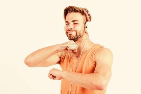 Photo pour La musique est tellement amusante. ebook et éducation en ligne. éducation musicale. sexy musclé homme écouter ebook. homme dans les écouteurs isolé sur blanc. Le livre. homme non rasé étude en ligne. - image libre de droit