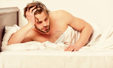 Photo pour Un jeune homme joyeux se réveille après avoir dormi le matin. Homme ressentant des maux de dos dans le lit après avoir dormi. Se réveiller détendu - image libre de droit