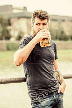 Photo pour Le type se repose avec de la bière fraîche. Hipster détendue boire de la bière en plein air. Café terrasse d'été. Des bières claires ou des stouts sombres les boivent toutes. Homme avec barbe et moustache tenir verre de bière à l'extérieur . - image libre de droit