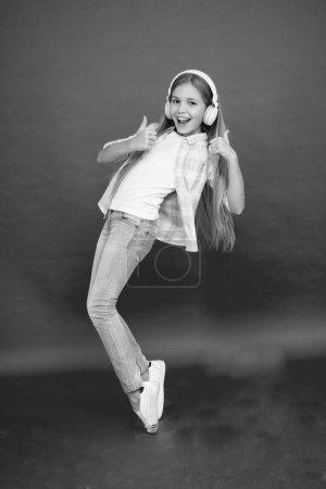 Photo pour Petite rock star. Le gamin hipster continue de bouger. casque enfant. danser avec la chanson préférée. bonheur d'enfance. enfant heureux écouter de la musique. vente et vacances d'été. Petite fille dans les écouteurs. fun en mouvement. - image libre de droit