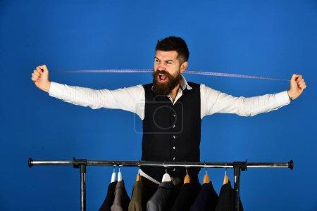Photo pour Homme à la barbe prend des mesures par porte-vêtements avec des costumes. Vendeur avec ruban à mesurer derrière le cou. Homme d'affaires avec un visage heureux près des vestes sur fond bleu. Mode et concept de style d'affaires - image libre de droit