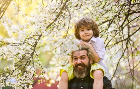 Fathers day. Child having fun with dad. Happy family. Little boy and father in nature background. Springtime. Hipster piggybacking baby. Bearded brutal man good father. Dad and son. Best dad ever
