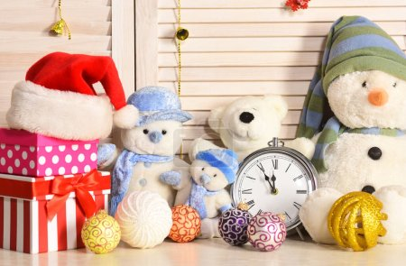 Photo for Toys placed on bureau on wooden wall background. Snowmen, teddy bears, Christmas balls and present boxes near alarm clock. Celebration and New Year decor concept. Christmas decorations in festive room - Royalty Free Image