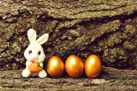 Photo for Future life, happy easter, rabbit toy with carrot, traditional golden eggs metallic color on tree bark background, farming, agriculture, luxury and success, riches, treasure, retirement, antique art - Royalty Free Image