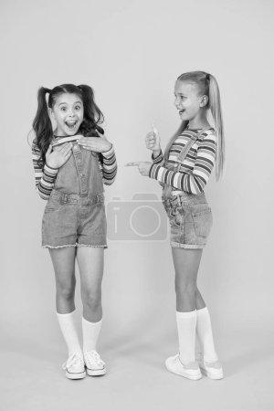 Photo pour Bonheur d'enfance. heureuse amitié scolaire. meilleurs amis pour toujours. Amuse-toi bien. petites filles fond jaune. salon de coiffure. Enfant mode d'été. beauté et style. Dans leur propre style. - image libre de droit