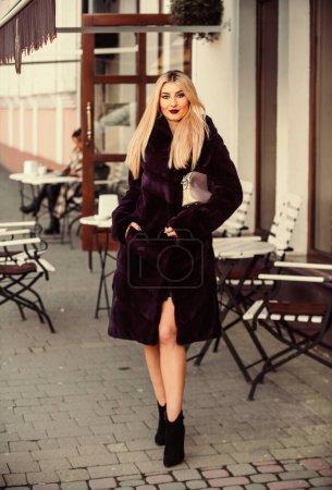 Photo pour Saison des fêtes. élégante femme porter manteau de fourrure. Respectueux de l'environnement. le meilleur matériel de vêtements de luxe. dame à l'air branché marcher dans la rue. confortable et chaleureux. compléter votre tenue. manteau de fourrure d'hiver moderne. - image libre de droit