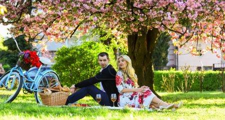 Photo pour Couple heureux et aimant se détendre dans le parc avec de la nourriture. Profitant de leur rendez-vous parfait. Couple amoureux pique-nique date. Week-end de printemps. Pique-nique romantique avec du vin. Offrez spontanément des cadeaux rares et uniques. - image libre de droit