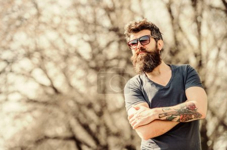 Photo for Bearded man wear modern fashionable sunglasses. UV filter. Man bearded with sunglasses nature background. Bearded hipster brutal man wear protective sunglasses. Hipster confident in dark sunglasses. - Royalty Free Image