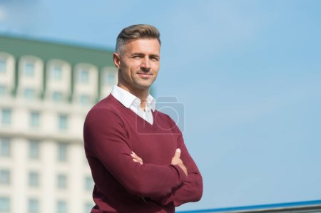 Attractive adult man. Handsome man blue sky background copy space. Rest and relax. Sunny spring day. Confident man. Good looking guy outdoor. Male beauty and fashion. Businessman in casual clothes