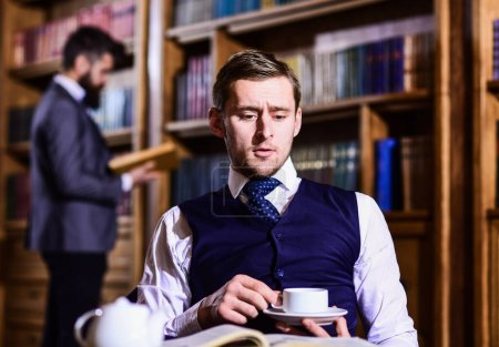 Photo for Blue blood concept. Young men with antique bookshelves on background. British elite or aristocrats spend leisure in library and drink tea. Intelligent or man in suit with good manners hold cup of tea. - Royalty Free Image