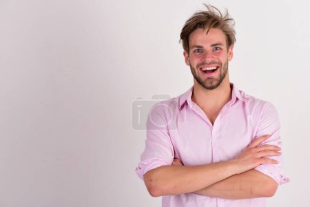 Photo pour Macho croise les bras. Masculinité et concept de style. Homme au visage souriant et joyeux sur fond blanc, espace de copie. Guy avec poils en chemise rose et cheveux salissants. - image libre de droit