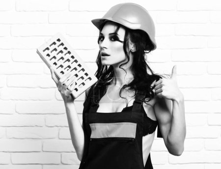 serious cute sexy builder girl on white wall background