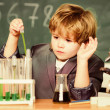 Small boy with microscope at school lesson. studen...