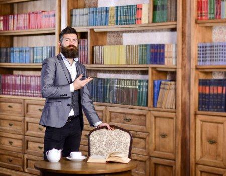 Photo pour Concept de bibliothèque d'accueil. Mature homme en costume formel montre la bibliothèque de la maison - image libre de droit
