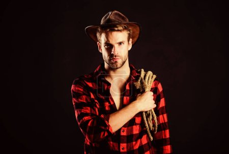 Photo pour Culture paysanne. chemise à carreaux homme sur ranch. cow-boy avec corde à lasso. Western. Homme de style vintage. Un cow-boy rétro du Far West. Portrait de cow-boy occidental. Wild West Rodeo. homme en chapeau fond noir. - image libre de droit