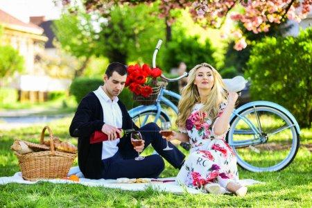 Photo pour Profiter du repos estival. famille heureuse dans le parc d'été. nourriture et boisson. homme et femme. couple romantique sur pique-nique. date d'amour au printemps. Détendez-vous sous sakura en fleurs. couple amoureux. célébration de l'anniversaire. - image libre de droit