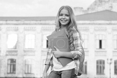 Photo pour Club scolaire. L'éducation moderne. Enseignement privé. Jeune avec sac à dos. Élégante écolière souriante. Fille petite écolière à la mode portent sac à dos fond de bâtiment de l'école. Écolière vie quotidienne. - image libre de droit