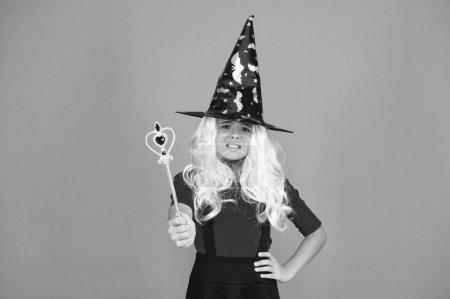 Simplemente feliz. niño encanto onda varita mágica. Feliz Halloween. cree en la magia. chica sonriente fiesta de halloween. La bruja misteriosa hace magia. Sombrero de bruja niño pequeño. truco o trato. encantador sobrenatural